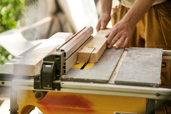 Haandvaerker der skaerer træ på maskine